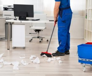 50690839 - low section of male janitor sweeping papers fallen on floor with broom in office
